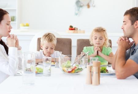 familia orando: Retrato de una familia rezando juntos durante el almuerzo