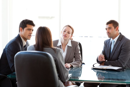 Rear view of a businesswoman being interviewed by three executives Stock Photo