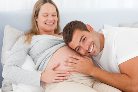 7 months: Happy future dad listening the belly of his pregnant wife Stock Photo