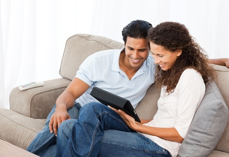 Lovely couple watching videos together sitting on their sofa Stock Photo - 10175580