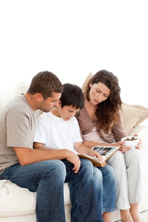 Adorable family looking at a photo album together on the sofa Stock Photo - 10175639