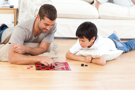 lying on the floor: Handsome man playing checkers with his son lying on the floor