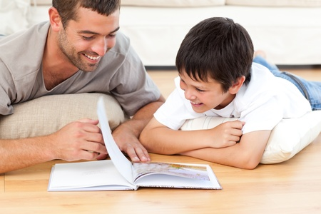 Cute boy reading a book with his father on the floor Stock Photo - 10174535