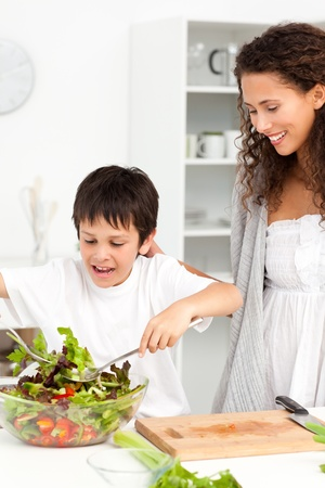 Cute boy mixing a salad with his mother in the kitchen photo
