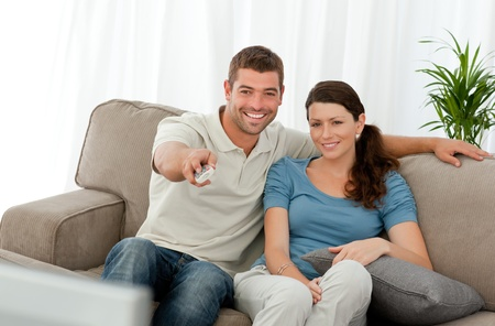 humoristic: Happy man watching television with his girlfriend sitting on the sofa