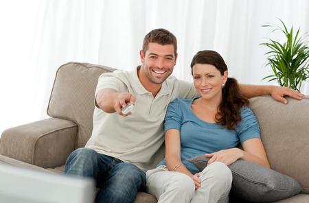 humoristic: Hombre feliz viendo la televisi�n con su novia sentado en el sof�