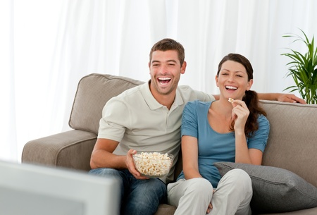Lovely couple laughing while relaxing in front of the television photo