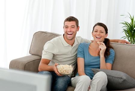 humoristic: Pareja encantadora riendo mientras se relaja delante de la televisi�n