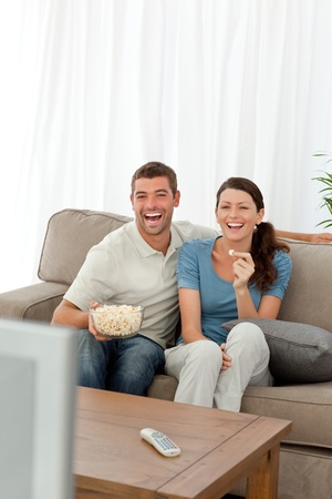 Cute couple eating pop corn while watching television on the sofa Stock Photo - 10175546