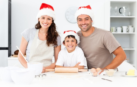 christmas cooking: Portrait of a happy family preparing christmas cookies Stock Photo