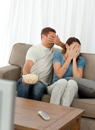 Lovely couple hiding their face from a horror movie sitting in the living-room photo