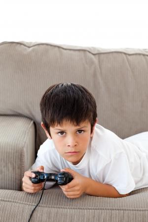 niños jugando videojuegos: Concentrado boy jugando videojuegos tirado en el sofá Foto de archivo