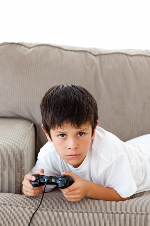 playing video games: Concentrated boy playing video games lying on the sofa