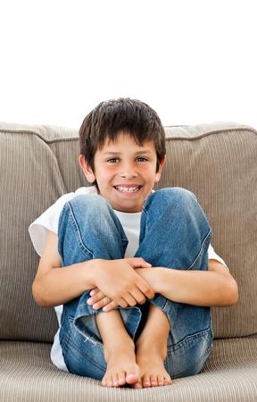 niños jugando videojuegos: Retrato de un adorable niño sentado en el sofá Foto de archivo