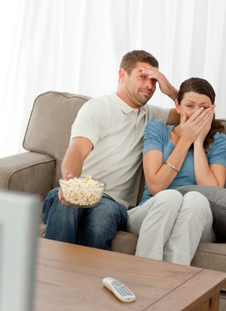 Terrified couple watching a horror movie photo