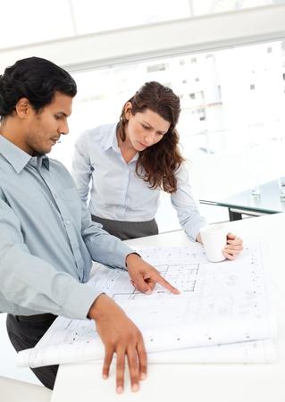 arquitecto: Arquitectos serios que buscan en los planes de pie en una mesa Foto de archivo