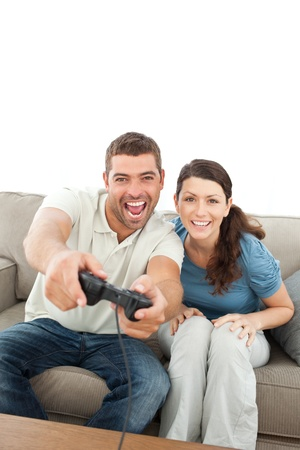 Happy couple playing video games together sitting on the sofa  Stock Photo - 10175572