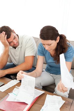 wanhopig: Stressed man en vrouw te kijken naar hun rekeningen in de huiskamer