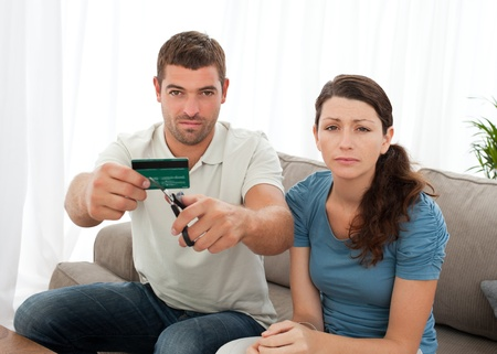 Worried couple cutting their credit card together sitting on the sofa Stock Photo - 10173603