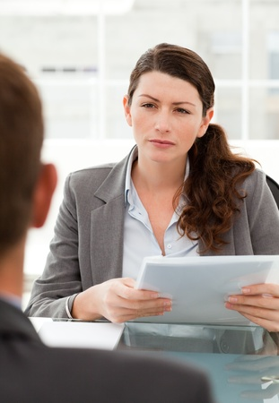 two companies: Serious businesswoman questionning a man during a meeting Stock Photo