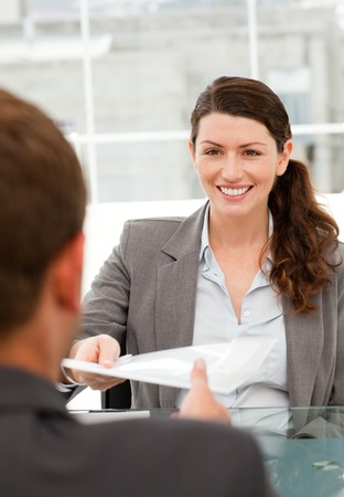 Happy businesswoman giving a paper to a male colleague during a meeting Stock Photo - 10174955