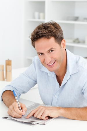 Smart man doing a cryptic crossword sitting in his kitchen Stock Photo - 10175499