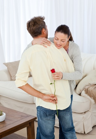 Hasty woman looking at rose hidden behind her boyfriend Stock Photo - 10173652
