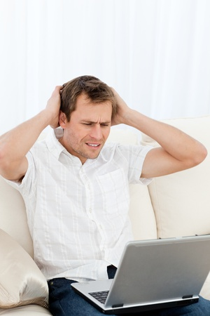 bothered: Tense man working on his laptop sitting on the sofa Stock Photo