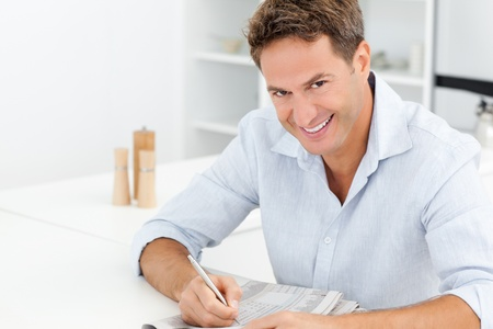 Happy man doing a crossword sitting at a table photo