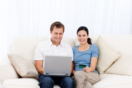 Happy couple buying online with laptop and credit card on the sofa Stock Photo - 10164175