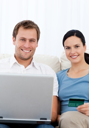 Lovely couple buying onllne while relaxing on the sofa Stock Photo - 10172717