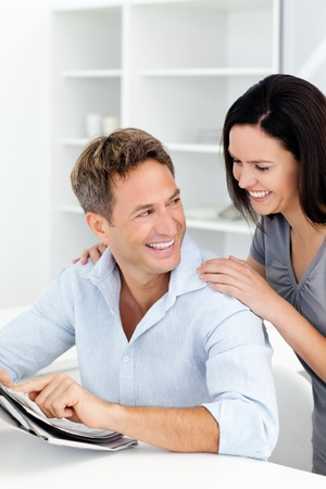 Happy man showing something on the newspaper to his girlfriend photo