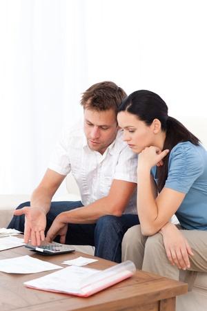 Desperate couple doing their account sitting on the sofa  Stock Photo - 10173294