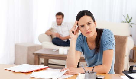 Worried woman doing her account while her boyfriend waiting in the living room photo