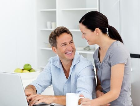 tabla de surf: Pareja feliz trabajando en su computadora port�til en la cocina