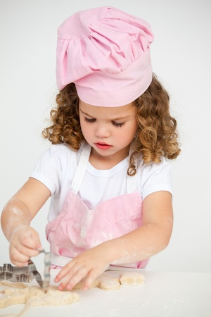 Cute little girl making biscuit at a table photo