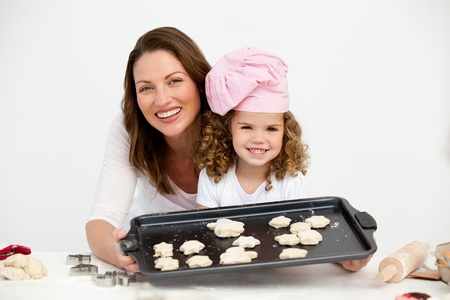 Happy mother and daughter showing a plate with biscuits photo