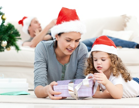 Mother and daughter unwrapping a present lying on the floor photo