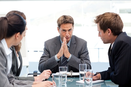 serious meeting: Serious manager talking to his team during a meeting