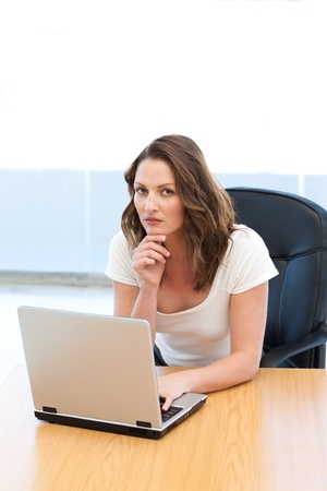 Attractive businesswoman working on laptop at a table photo