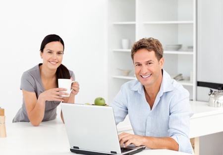 hombre tomando cafe: Retrato de un hombre que trabaja en la computadora port�til, mientras que su novia est� tomando caf� Foto de archivo