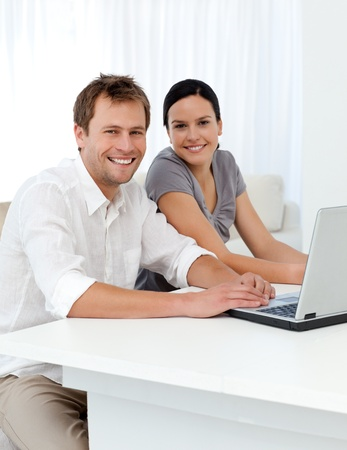 Portrait of a couple with a laptop at a table in the living room  photo