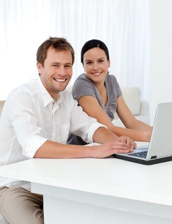 pareja en casa: Retrato de una pareja con un ordenador port�til en una mesa en la sala de estar