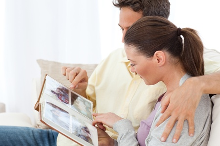 Lovely couple looking at pictures on a photo album on the sofa Stock Photo - 10175652