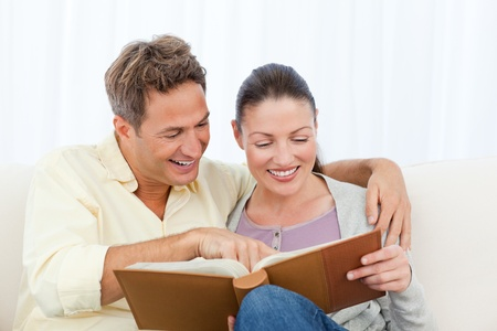 Couple smiling while looking at pictures on a photo album Stock Photo - 10175438