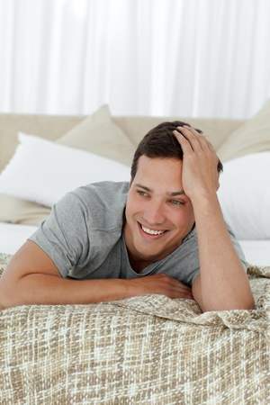 unbend: Happy man smiling lying on his bed Stock Photo