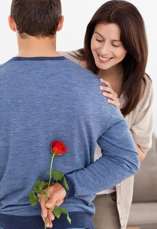 Impatiente woman looking at a flower hidden by her boyfriend photo