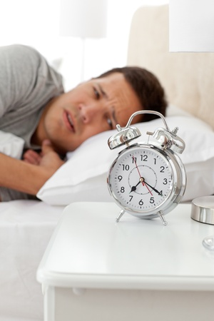 bothered: Unhappy man looking at his alarm clock while lying on his bed