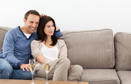Relaxed couple watching television while drinking champagne Stock Photo - 10175605