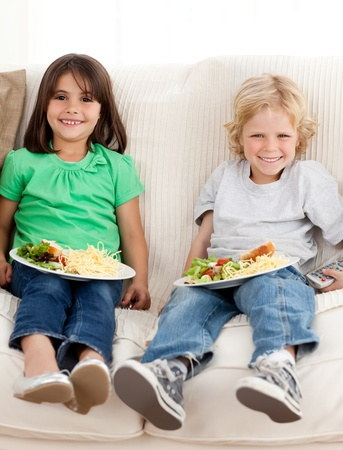 Happy brother and sister watching television while eating pasta photo